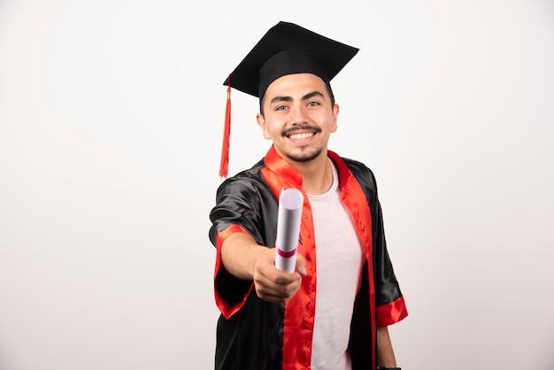 Gelukkige mannelijke student die zijn diploma op wit toont.