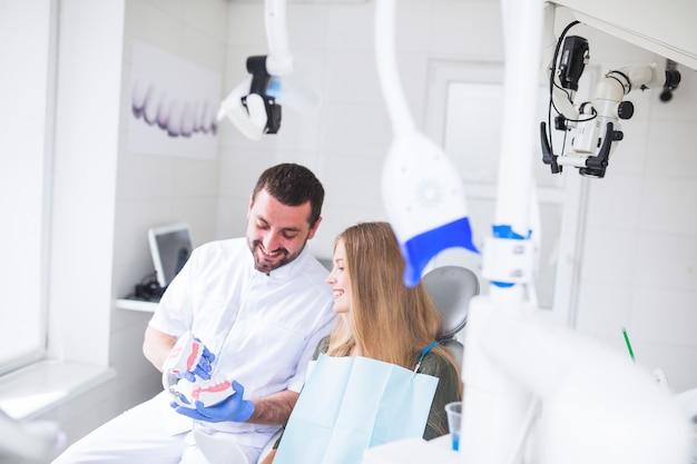 Gelukkige mannelijke tandarts die tandenmodel toont aan patiënt