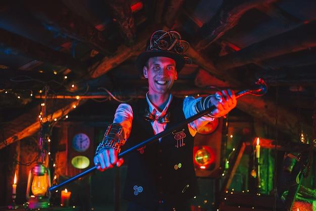 Gelukkige mannelijke uitvinder in een steampunk-pak, hoge hoed, bril en met een rietglimlach in een horlogewerkplaats met een neonlicht