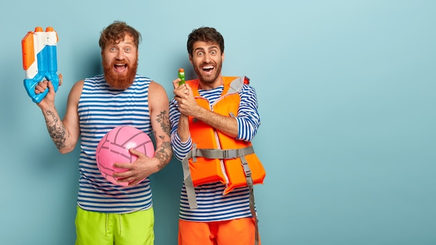 Gelukkige mannelijke vrienden hebben plezier op het strand, spelen met waterpistolen, bal