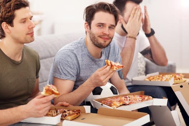 Gelukkige mannelijke vrienden juichen en kijken naar sport op tv