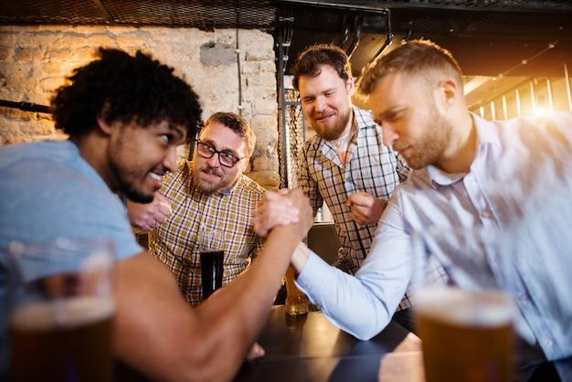 Gelukkige mannelijke vrienden van gemengd ras met armworstelen uitdaging in de lokale bar met een biertje vooraan.