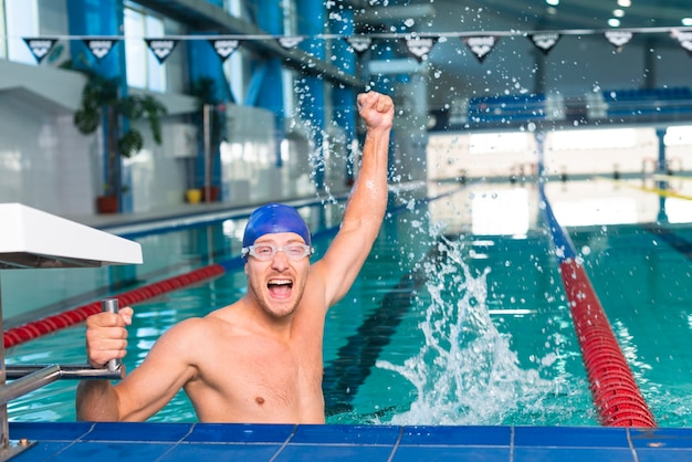 Gelukkige mannelijke zwemmer die zijn hand opheft
