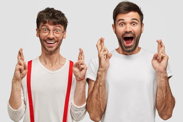 Gelukkige mannen anticiperen op de resultaten van het examen, steken vingers over elkaar als ze geloven in geluk, staan dicht bij elkaar, zijn erg emotioneel, geïsoleerd over een witte muur. mensen, lichaamstaal en wensconcept