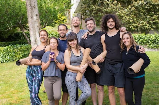 Gelukkige mannen en vrouwen uit de yogaclub met plezier