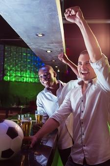 Gelukkige mannen kijken naar een voetbalwedstrijd in bar