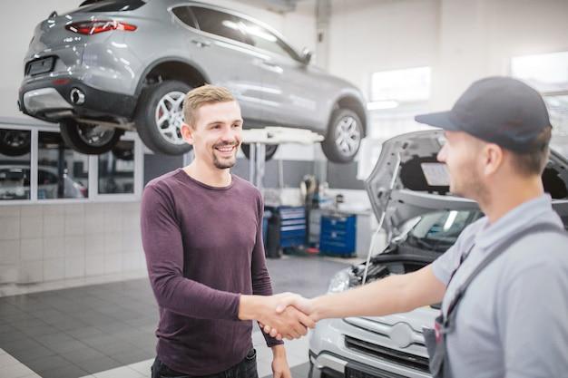Gelukkige mannen staan in de garage en schudden elkaar de hand. ze staan voor de geopende auto. er staat een ander voertuig achter de blonde man op het platform.
