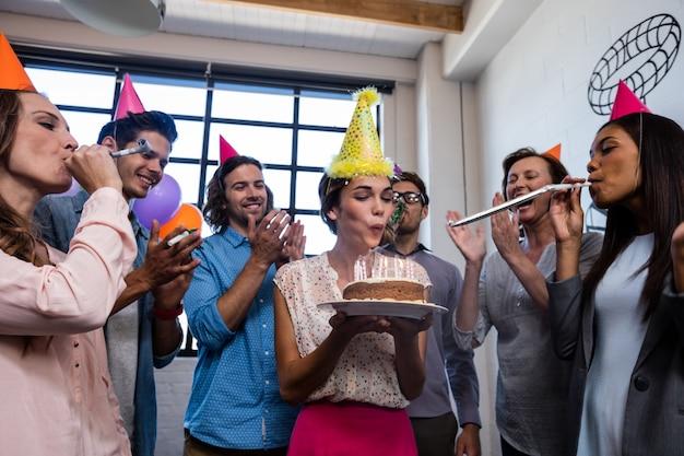Gelukkige medewerker blazende kaarsen voor verjaardag
