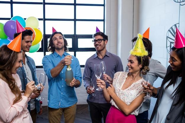 Gelukkige medewerker die een fles champagne voor verjaardag opent