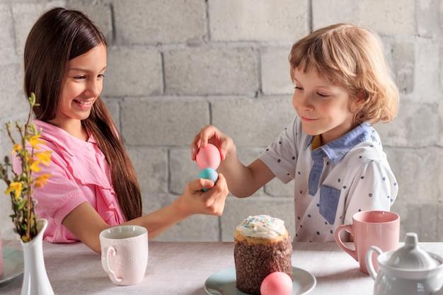 Gelukkige meisje en jongen die traditioneel pasen-spel spelen - ei dat met gekleurde eieren thuis tikt