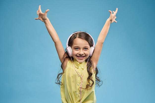 Gelukkige meisje het luisteren muziek in hoofdtelefoon en het opheffen van handen omhoog