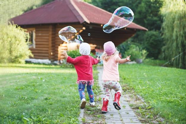 Gelukkige meisjes die buiten met zeepbellen spelen