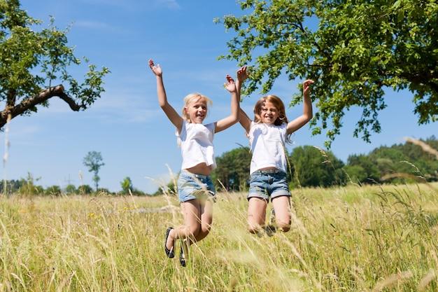 Gelukkige meisjes die in de weide springen