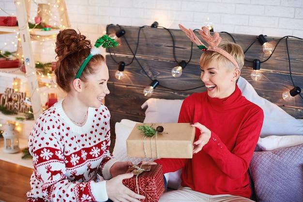 Gelukkige meisjes die kerstmis in bed vieren