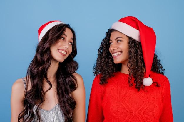 Gelukkige meisjes die kerstmishoeden dragen die over blauw worden geïsoleerd