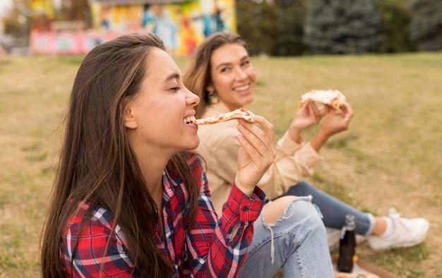 Gelukkige meisjes die pizza buiten eten