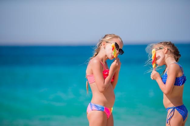 Gelukkige meisjes die roomijs eten tijdens strandvakantie. mensen, kinderen, vrienden en vriendschapsconcept