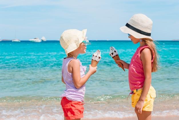 Gelukkige meisjes die roomijs eten tijdens strandvakantie.