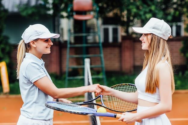 Gelukkige meisjes die tennis spelen, handen schudden, glimlachen, tijd samen doorbrengen.