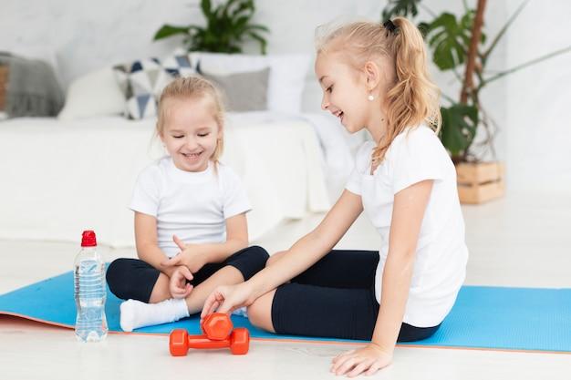 Gelukkige meisjes die thuis op yogamat uitoefenen met gewichten
