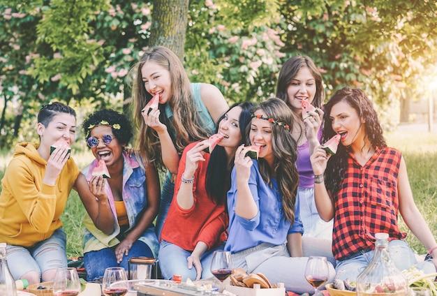 Gelukkige meisjes die watermeloen eten bij picknickdiner in de tuin