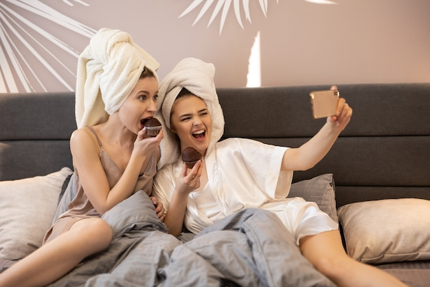 Gelukkige meisjes eten chocoladetaarten en nemen selfie op mobiele telefoon op bed. jonge europese vrouwen met ingepakte badhanddoeken op hoofden. concept van meisjesfeest thuis. interieur van slaapkamer in modern appartement
