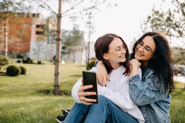 Gelukkige meisjes in een park die glimlachen en zelfportretten maken met een smartphone
