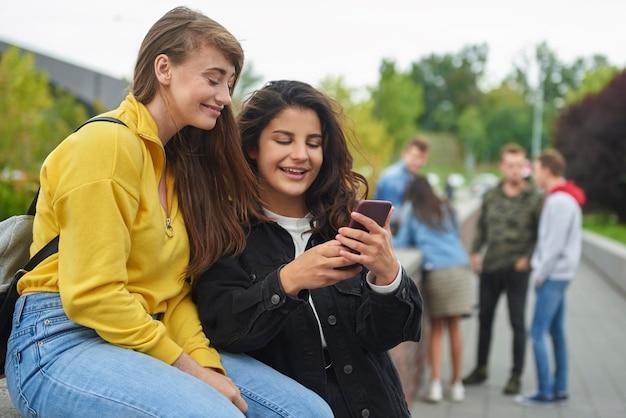 Gelukkige meisjes kijken naar slimme telefoon