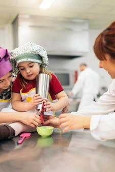 Gelukkige meisjes koken in een keuken. koken concept.