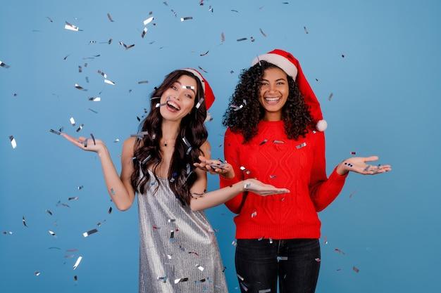 Gelukkige meisjes met confetti in de lucht dragen kerstmutsen