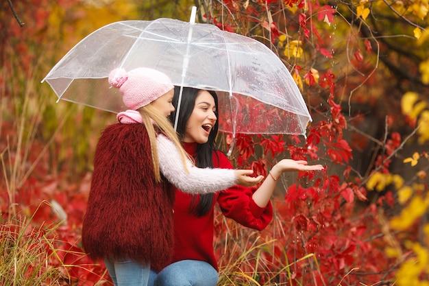 Gelukkige meisjes op heldere herfst plezier samen.