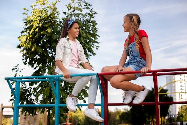 Gelukkige meisjes praten op de speelplaats