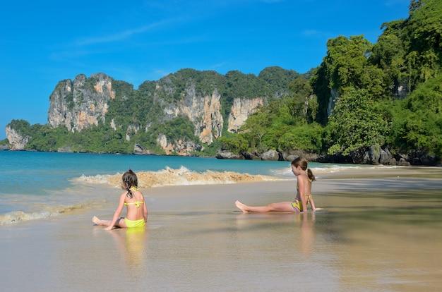 Gelukkige meisjes spelen in zee op tropisch strand