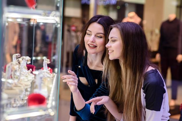 Gelukkige meisjes winkelen in de mall.