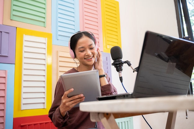Gelukkige meisjesblogger die in de microfoon praat tijdens het lezen met een pad