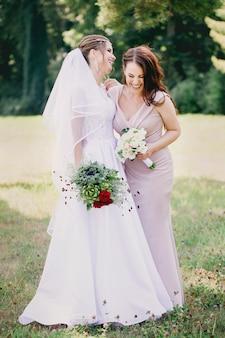 Gelukkige meisjesbruid en bruidsmeisje met boeketten