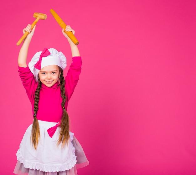 Gelukkige meisjeskok die zich met keukengerei bevinden