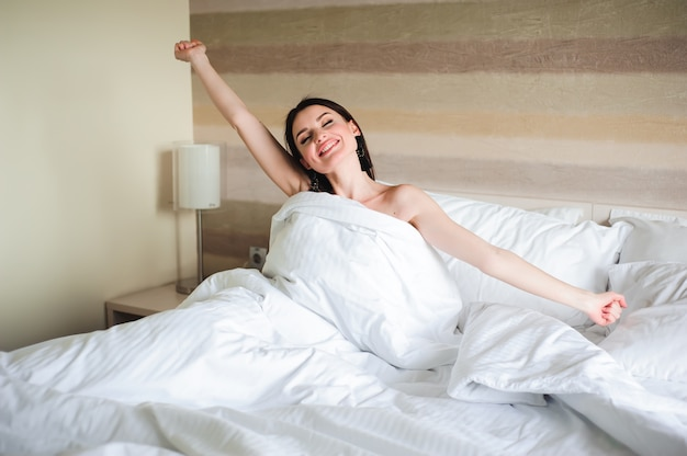 Gelukkige meisjesontwaken die wapens op het bed in de ochtend uitrekken zich.