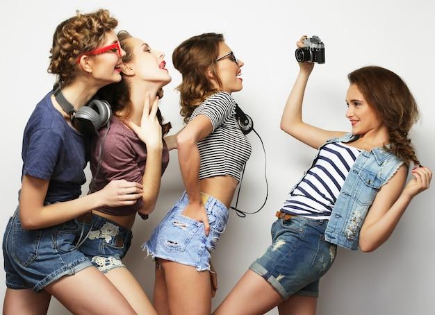 Gelukkige meisjesvrienden die enkele foto's nemen, over grijze achtergrond
