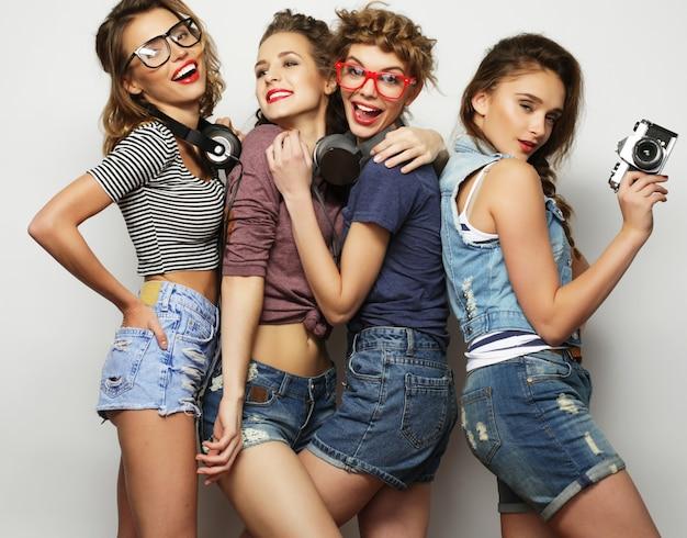 Gelukkige meisjesvrienden die enkele foto's op grijs nemen