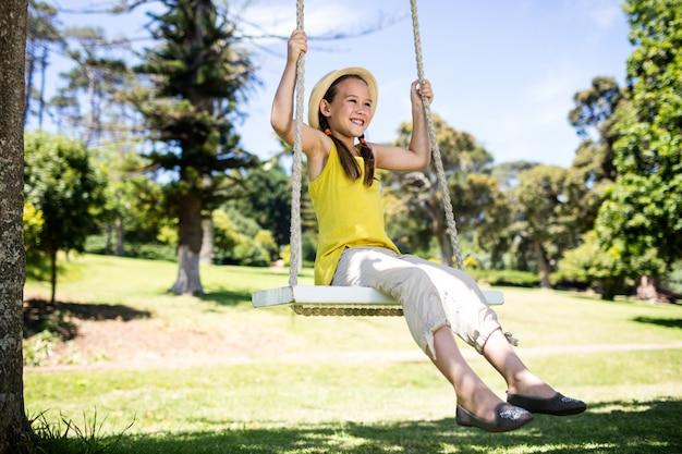Gelukkige meisjeszitting op een schommeling in het park