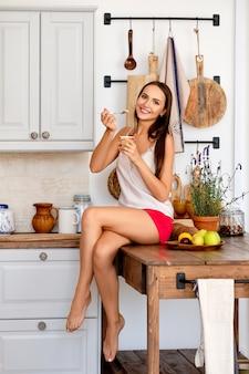 Gelukkige meisjeszitting op keukenlijst en het eten van yoghurt