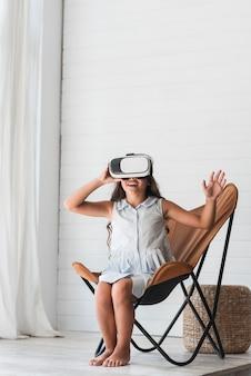 Gelukkige meisjeszitting op stoel die virtuele werkelijkheidsglazen thuis dragen