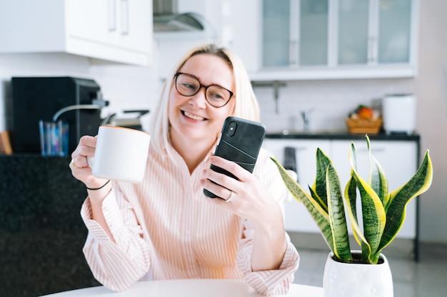 Gelukkige meisjeszitting thuis keuken en holdings videocall. jonge vrouw die smartphone gebruiken voor videogesprek met vriend of familie. vlogger-opname webinar. vrouw die camera kijkt en groethanden golft