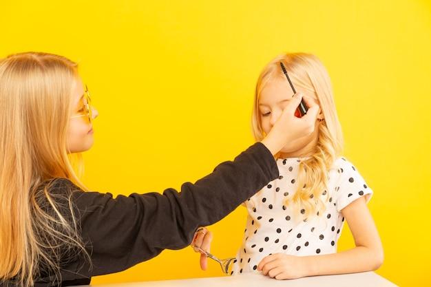 Gelukkige meisjeszusjes thuis voor camera die vlog maken. werken als blogger, video-tutorials opnemen voor internet.
