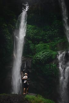 Gelukkige mens die backpacker van verbazende tropische waterval op aardlandschap genieten. reizen lifestyle en succes concept vakanties in de wilde natuur op bergen en regenwoud
