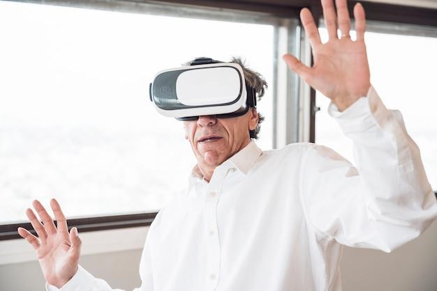 Gelukkige mens die de simulatie van de virtuele werkelijkheidshoofdtelefoon onderzoeken