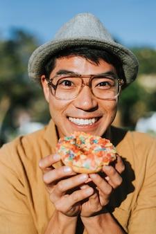 Gelukkige mens die een doughnut heeft