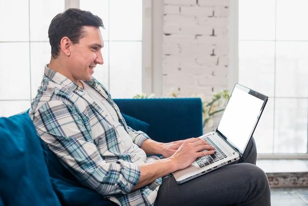 Gelukkige mens die en op laptop zit gebruikt