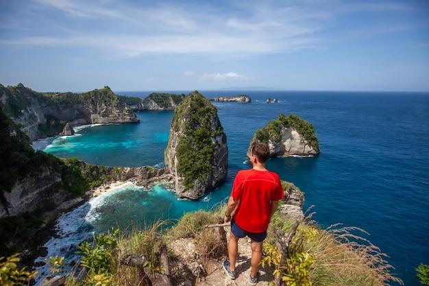Gelukkige mens die en zich op het rots duizend eilandgezichtspunt nusa penida bevinden kijken